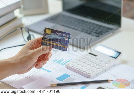 Man Holding Mock Up Credit Card For Shopping Online With Calculator,laptop And  Financial Report. Pa