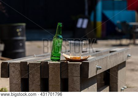 Empty Green Bottle And Plastic Cup On Rustic Table. Unfilled Bottle Of Bear With Empty One-time Use