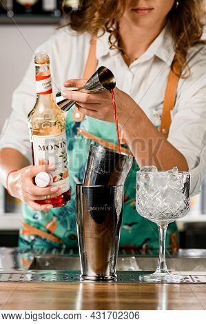 Ukraine, Kyiv - March 12, 2021: Female Bartender Holds Jigger And Pours Drink Into Shaker. Bottle Of