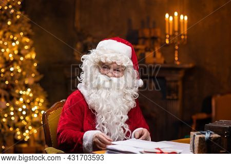 Workplace of Santa Claus. Cheerful Santa is working while sitting at the table. Fireplace and Christmas Tree in the background. Christmas concept.