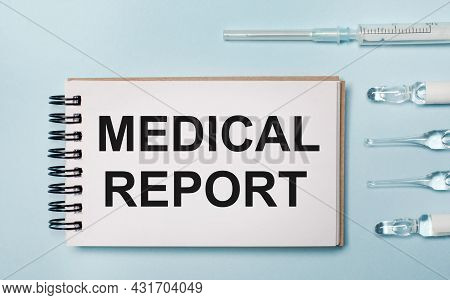 On A Blue Background Ampoule With Medicines And A Notebook With The Text Medical Report. Medical Con