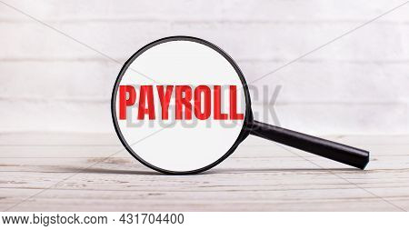 The Magnifying Glass Stands Vertically On A Light Background With The Text Payroll