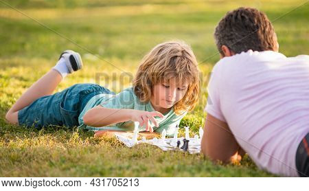 Happy Family Of Dad And Son Child Playing Chess On Green Grass In Park Outdoor, Tactic
