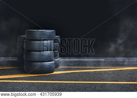 Tire Pile On The Asphalt Road With Smoke At Night And Black Background,copy Space