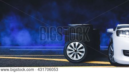Wheel And Tire Pile On The Asphalt Road And Blue Smoke With Black Background At Night