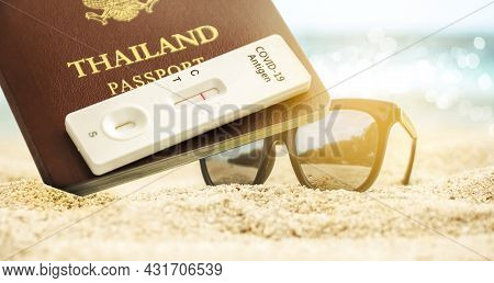 Thailand Passport And Covid-19 Antigen Test Kit With Negative Test Result And Sunglass Placing On Th