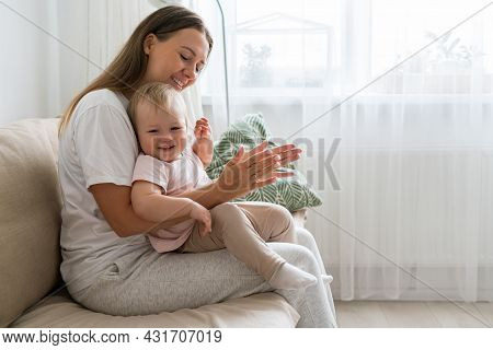 Horizontal Of Smiling Mom Clapping And Looking At Happy Baby Girl Sitting On Couch In Living Room. M
