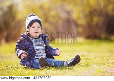 Cute little boy playing in the autumn park. Beauty nature scene with colorful background at fall season. Family outdoor lifestyle. Happy kid relax on grass, having fun outdoor. Happiness in childhood
