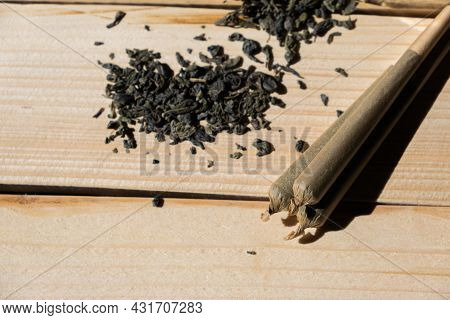 Close-up Of Three Cannabis Joint With Chopped Marijuana On Wooden Table. Concept Of Therapeutic Cann