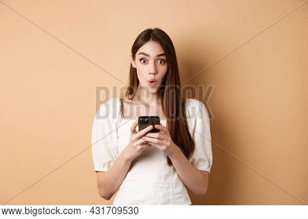 Girl Standing Amazed With Smartphone, Saying Wow And Look Excited By Awesome Online Offer News, Stan