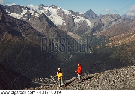 People Are Engaged In Nordic Walking In The Mountains. An Active Couple Is Engaged In Hiking. A Youn