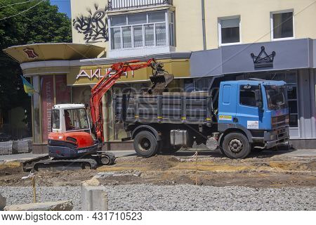 Lutsk, Ukraine - July 08, 2021: Excavator And Truck Are Working. Excavation Work During The Renovati