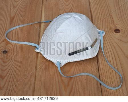 Construction Dust Protection Mask. Respiratory Health. White Protective Mask On A Wooden Background