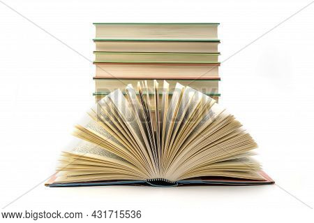 Stack Of Books With One Book Open On White Background. A Stack Of Books Of Different Thicknesses, A