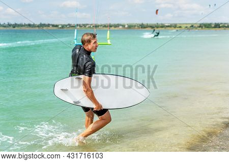 Back View Of Young Adult Caucasian Fit Male Person Enjoy Riding Kite Surf Board In Sun Uv Protection
