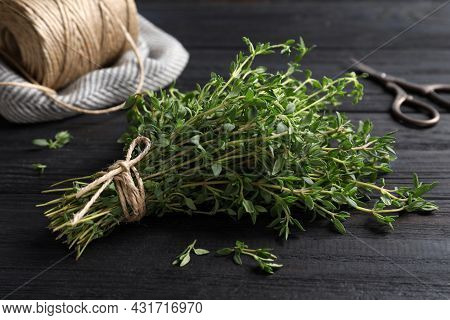 Bunch Of Aromatic Thyme, Scissors And Twine On Wooden Table, Closeup