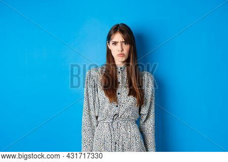 Moody Frowning Girl In Dress Looking At Unfair Thing, Standing Offended Or Upset Against Blue Backgr