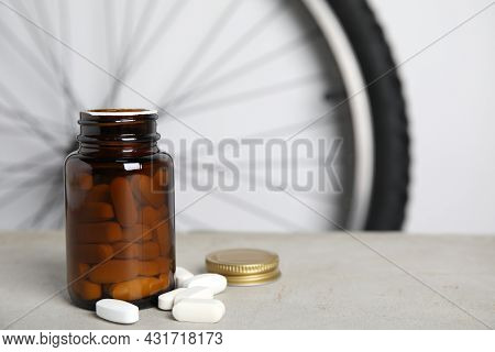 Pills On Light Grey Table Near Bike Wheel, Space For Text. Using Doping In Cycling Sport Concept