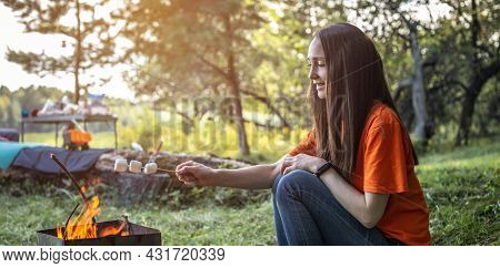 A Young Happy Girl Is Roasting Marshmallows On The Fire And Enjoying A Rest In Nature. Concept Of Sp