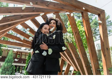Cheerful Multiethnic Lesbian Couple In Suits Hugging Near Petals During Wedding In Park