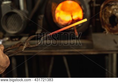 Close-up Working Powerful Hands Of Male Blacksmith Making Red Hot Metal In Furnace, Horn. Work Proce