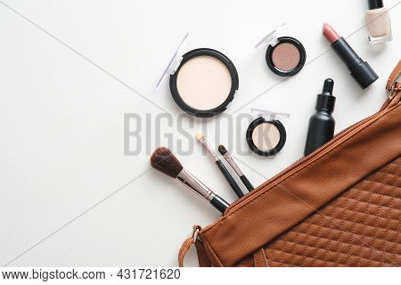Flat Lay Pouch Of Professional Makeup Cosmetics And Tools On Brown Background. Top View With Copy Sp