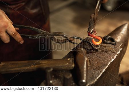 Close-up Working Powerful Hands Of Male Blacksmith Forge An Iron Product In A Blacksmith. Hammer, Re
