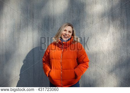 Happy Positive Middle-aged Woman In Orange Down Jacket Smiling At Camera While Posing Against Concre
