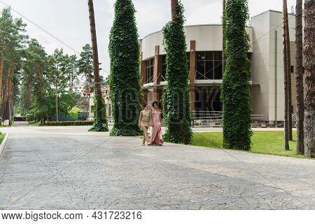 Multiethnic Lesbian Couple In Formal Wear Walking On Urban Street