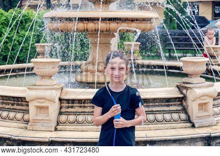Krasnodar, Russia - August 31 2021: Near The Fountain. Girl Having Fun With Fountain At Hot Sunny Da