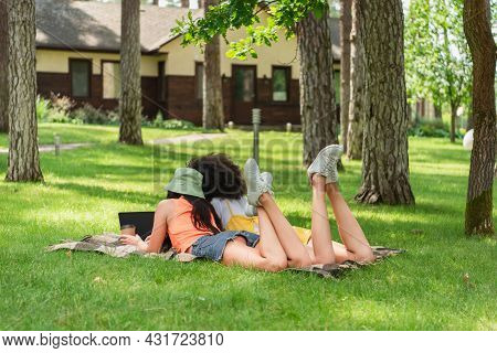 Back View Of Multiethnic Lesbian Couple Using Laptop Near Coffee On Blanket In Park