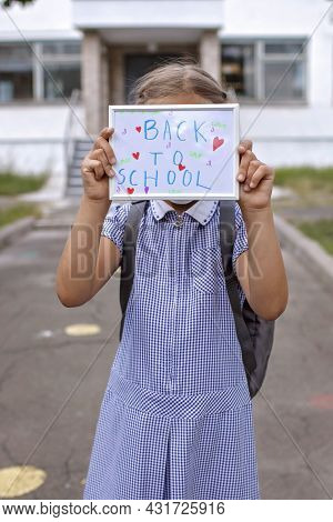 Elementary School Girl In Medical Mask Holds Picture With Back To School Message. First Offline Day