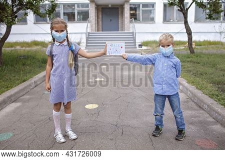 Elementary School Siblings In Medical Mask Hold Picture With Back To School Message. First Offline D