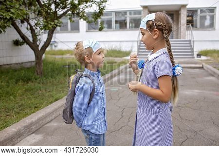 Back To School. Elementary School Kids. Siblings With Backpacks In Medical Masks Talks Together Befo