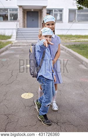 Back To School. Elementary School Kids. Siblings With Backpacks In Medical Masks Have Fun Near Doors
