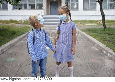 Back To School. Elementary School Kids. Siblings With Backpacks In Medical Masks Stay Near School Do