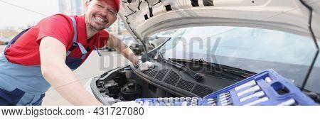 Smiling Repairman In Uniform Fixing Car With Tools