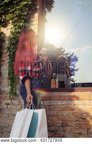Fashionably Dressed Girl At The Window Of A Boutique Selling Clothes. A Woman Holds A Mini Chihuahua