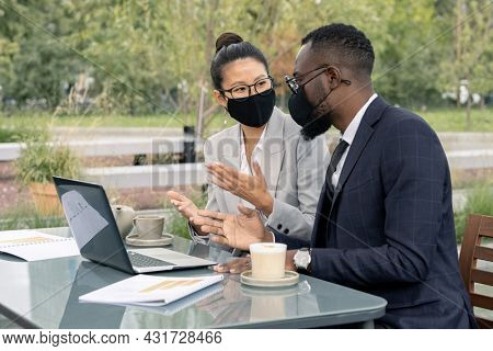 Two confident white collar workers in formalwear and protective masks discussing new business project in outdoor cafe