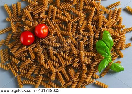 Raw Fusilli Pasta Lie In A Heap With Cherry Tomatoes And A Sprig Of Basil On A Gray Background. Whol