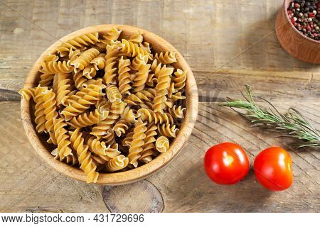 Raw Fusilli In A Wooden Bowl On A Cutting Board With Cherry Tomatoes And Rosemary On A Wooden Table.