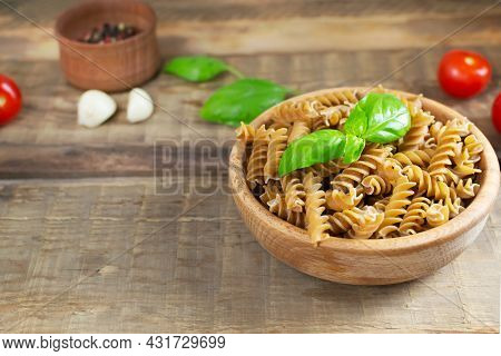 Raw Fusilli In A Wooden Bowl On A Cutting Board With Cherry Tomatoes And Basil On A Wooden Table. Ru