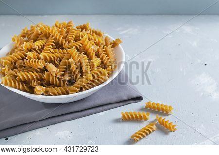 Raw Fusilli In A White Bowl On A Gray Napkin On A Gray Background. Italian Cuisine Concept. Copy Spa