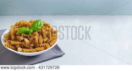 Raw Fusilli In A White Bowl On A Gray Napkin With A Sprig Of Basal On A Gray Background. Time To Eat