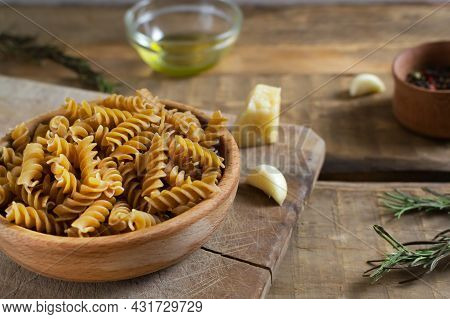 Raw Fusilli In A Wooden Bowl On A Cutting Board With Ingredients On A Wooden Table. Rustic Style. Ho