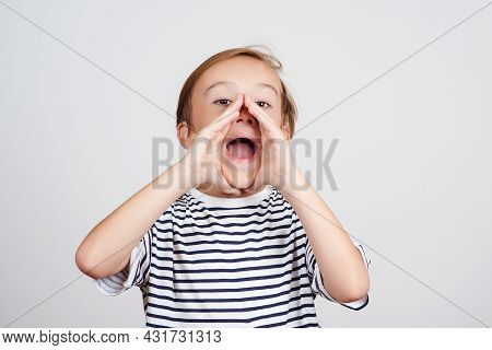 Cute Child Shouting Over White Background. Boy Opening Mouth Widely And Holding Hands On His Cheeks.