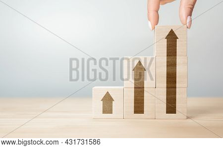 Hand Arranging Wood Block With Arrow Up Icon. Cropped Hand Of Person Stacking Wooden Blocks On Table