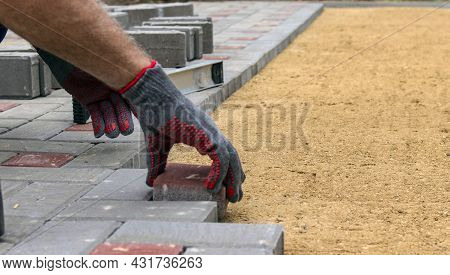 A Craftsman In Gloves With A Rubber Mallet Lays Concrete Blocks On A Gravelly Sand Base. A Craftsman