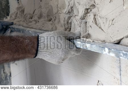 The Worker Levels The Plaster With A Leveler