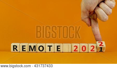 Planning 2022 Remote New Year Symbol. Businessman Turns Wooden Cubes And Changes Words 'remote 2021'